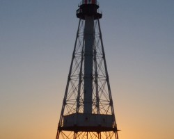 a view of the sunset through alligator lighthouse on a flat calm night as the sun paints the sky bright orange in Islamorada not too far from sombrero light at sombrero reef in marathon